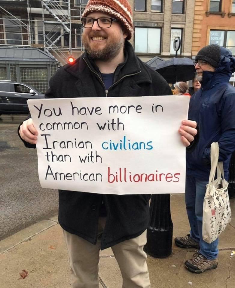 """Sympathisch lächelnder Mann (vermutlich US-Amerikaner) - der ein Schild hält auf dem steht: """"You have more in common with Iranian civilians than with American billionaires."""" (Ich hoffe das ist gerade noch politisch korrekt zu sagen. Wenn nicht möchte ich mich Entschuldigen.)"""